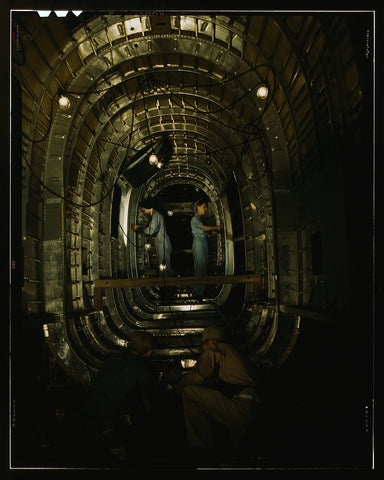 Installing structural parts of a C-87 transport plane in the tunnel of a tail fuselage section at the Consolidated Aircraft Corporation plant Fort Worth Texas