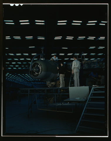 Lowering an engine in place in assembling a transport plane in a Consolidated Aircraft Corporation plant Fort Worth Texas