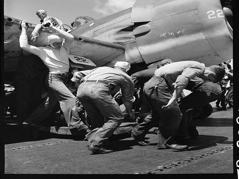 Crewmen hastily drag plane with flat tire down flight deck of USS Lexington (CV-16) to make way for next plane to land.