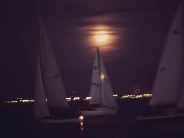 MOONLIGHT SAILBOAT RACE ON COMMENCEMENT BAY. LIGHTS OF TACOMA IN BACKGROUND