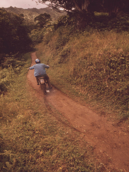 MOTORCYCLIST ON FOOT TRAIL LEADING TO WAIPAHEE FALLS  A SCENIC AREA MAINTAINED BY THE STATE FORESTRY DEPARTMENT