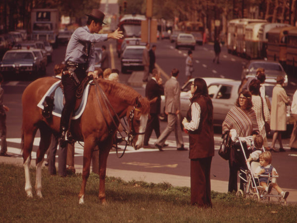 MOUNTED POLICEMAN ON BUSY DOWNTOWN THOROUGHFARE