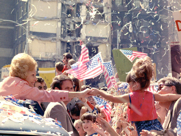 Mrs.Nixon reaching out to a little girl from her car in a campaign motorcade in Atlanta, Georgia.