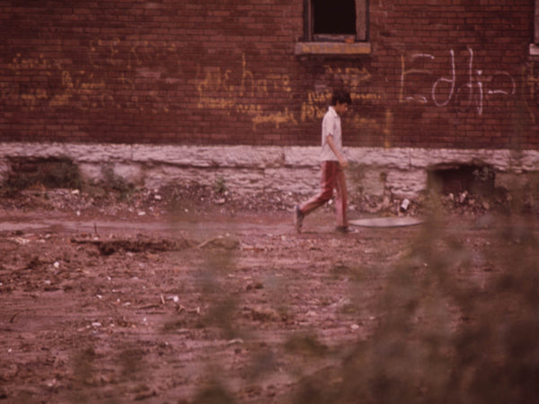 MULKY SQUARE BOY WALKS PAST BUILDING MARKED FOR DEMOLITION TO MAKE WAY FOR A NEW INTERSTATE HIGHWAY (I-635).