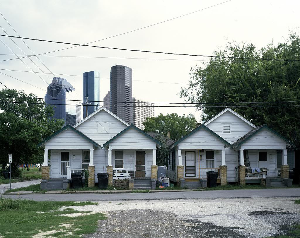 Small row houses sit close to the high-rise buildings in Houston Texas