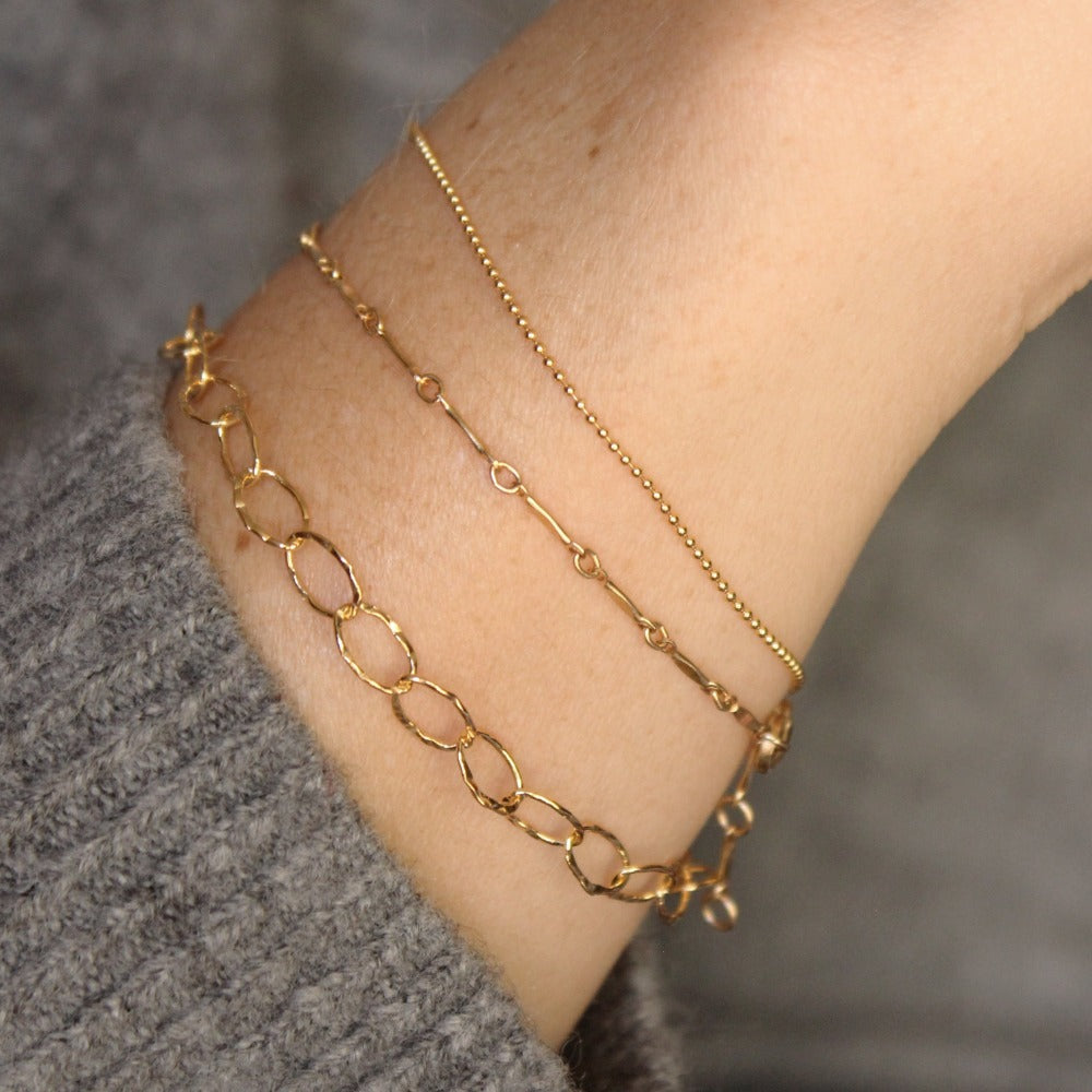 Hammered Oval Link Bracelet | Magpie Jewellery | Yellow Gold | On Model | Layered with Dapped Bar and Tiny Ball Chain Bracelets, Left-to-Right