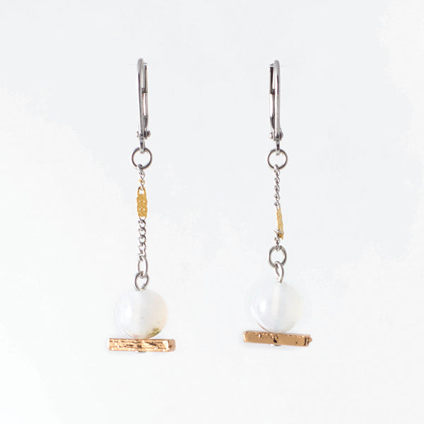Pictured: drop earrings on white background, composed of a surgical steel leverback closure connected by a jump loop to a pewter chain interrupted by a gold component before attaching by a second jump loop to, first, a polished spherical agate, and then a bronze-coloured narrow bar.