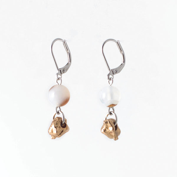 Pictured: drop earrings on white background, composed of a surgical steel leverback closure connected by a jump loop to a spherical, polished agate, which then connects by another jump loop to a small, bronze-coloured nugget. The agates are pale, but both feature warm, reddish-brown inclusions. The left stone is a slightly warmer colour than the right, and the inclusions vary in each.