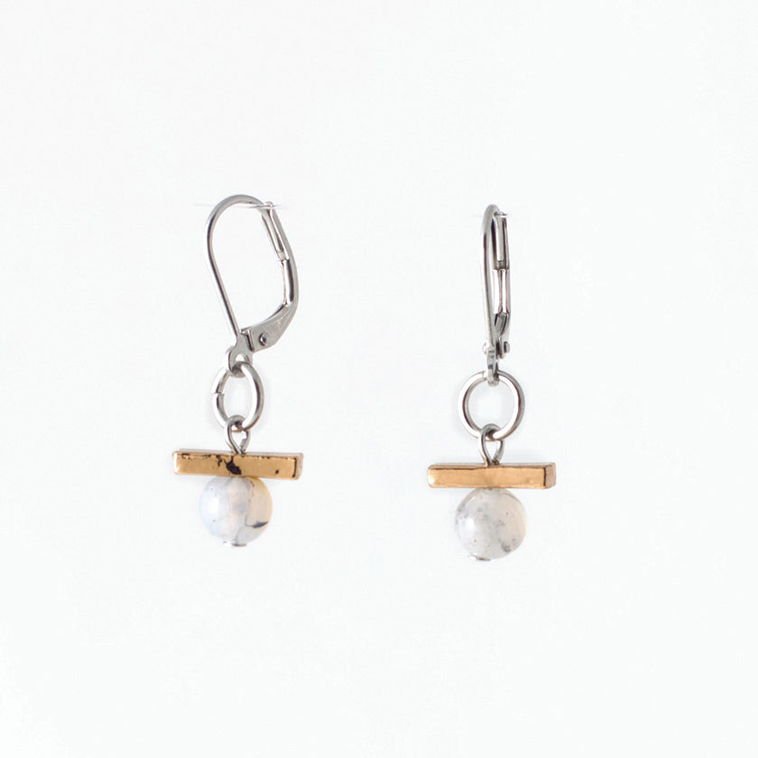 Pictured: drop earrings on white background, composed of a surgical steel leverback closure connected by a jump loop to a horizontal bronze-coloured bar set atop a pale agate stone. The agates are spherical and polished, and appeared to be drilled through, as the silver-coloured disc at the end of the bead pin is slightly visible at the bottom. Faint greyish speckling is visible in both stones.