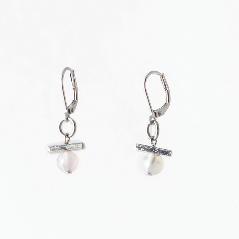 Pictured: drop earrings on white background, composed of a surgical steel leverback closure connected by a jump loop to a horizontal pewter bar set atop a pale agate stone. The agates are spherical and polished, and appeared to be drilled through, as the silver-coloured disc at the end of the bead pin is slightly visible at the bottom.