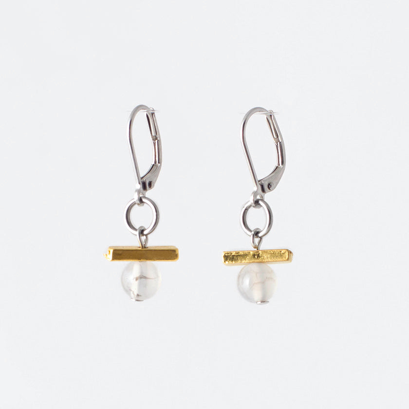 Pictured: drop earrings on white background, composed of a surgical steel leverback closure connected by a jump loop to a horizontal gold-coloured bar set atop a pale agate stone. The agates are spherical and polished, and appeared to be drilled through, as the silver-coloured disc at the end of the bead pin is slightly visible at the bottom. Faint greyish inclusions are visible in both, though more visible in the left.