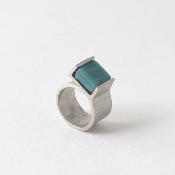 Pictured: Bello ring in 'Aquatic' against flat white background. The ring is a wide flat strip of pewter that curls back on itself but is not soldered. At the end of the overlap, a square piece of green-blue opaque glass has been set in a half-bezel.