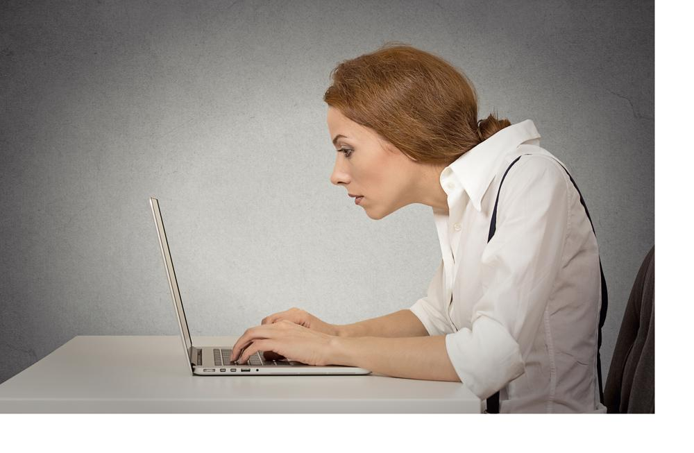 Woman sitting at desk with bad ergonomic posture