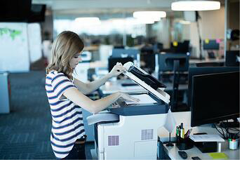 Young business woman using copy machine in office