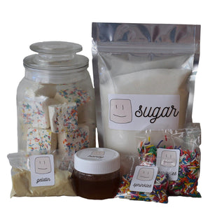 ingredients in the marshmallow making kit, bag of sugar, jar of honey, packs of gelatin and sprinkles