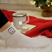 Load image into Gallery viewer, model's leg with logo white socks on, with logo mug with hot chocolate and marshmallow on top of a book