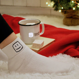 model's leg with logo white socks on, with logo mug with hot chocolate and marshmallow on top of a book