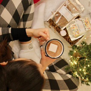 birds eye view of woman wearing pajamas and the logo socks, holding the logo mug with hot chocolate, and the cozy kit next to her