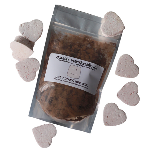 Pack of hot chocolate mix, containing chocolate chunks, cocoa powder and sugar, with strawberry pink marshmallow hearts surrounding it