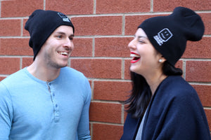 Male and female models wearing the beanies, smiling