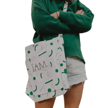 Load image into Gallery viewer, A close up of the middle of a woman wearing denim shorts, a green jumper and wearing a white tote bag with a green confetti pattern and the word JAM on it. Her arms are crossed and the background is plain white.