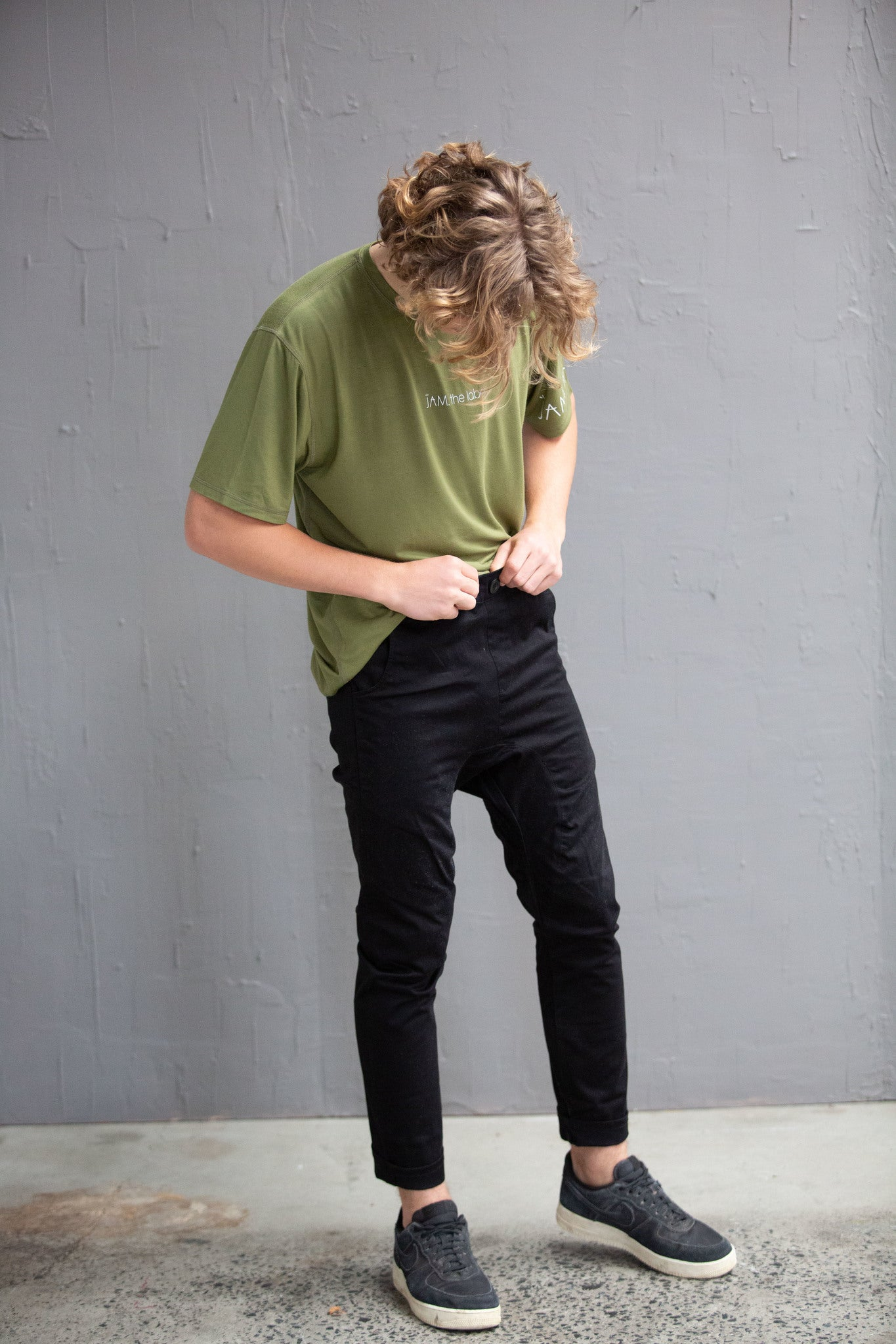 A young white man with blonde curly hair is standing in front of a grey wall. He is looking down at himself. He is wearing an olive green top, black chinos and black shoes.