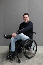 "Load image into Gallery viewer, Jason, a white man with short brown hair, is sitting in his wheelchair and smiling. He is wearing a black long sleeve with the words ""JAM the label"" down the sleeve, ripped light blue jeans and black boots. One leg is crossed over the other. He is against a grey wall and the floor is concrete."