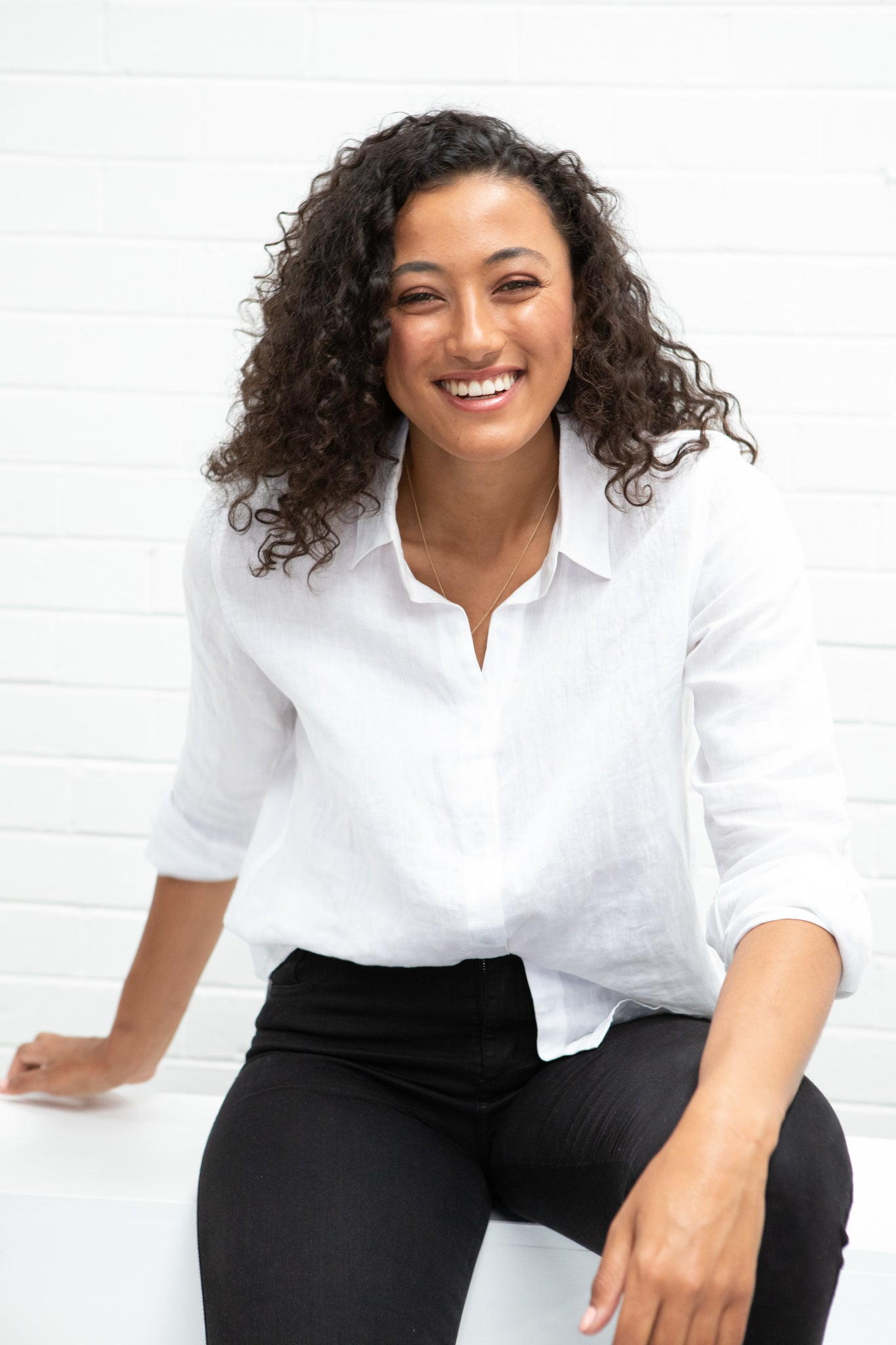 A model wearing a white linen shirt and black pants