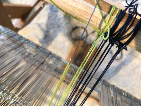 pulling the yarn through the heddle