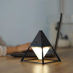 Black ceramic table lamp pyramid with LED in living room