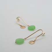 curve earrings in glossy gold with mint green recycled glass drops lying flat