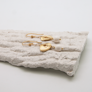gold disc earrings with ivory bead lying on decorative plasterwork bark
