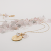 rose quartz matte gold disc necklace lying flat beside rose quartz stones