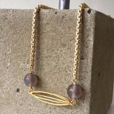 matte gold cocoon necklace with grey agate stones