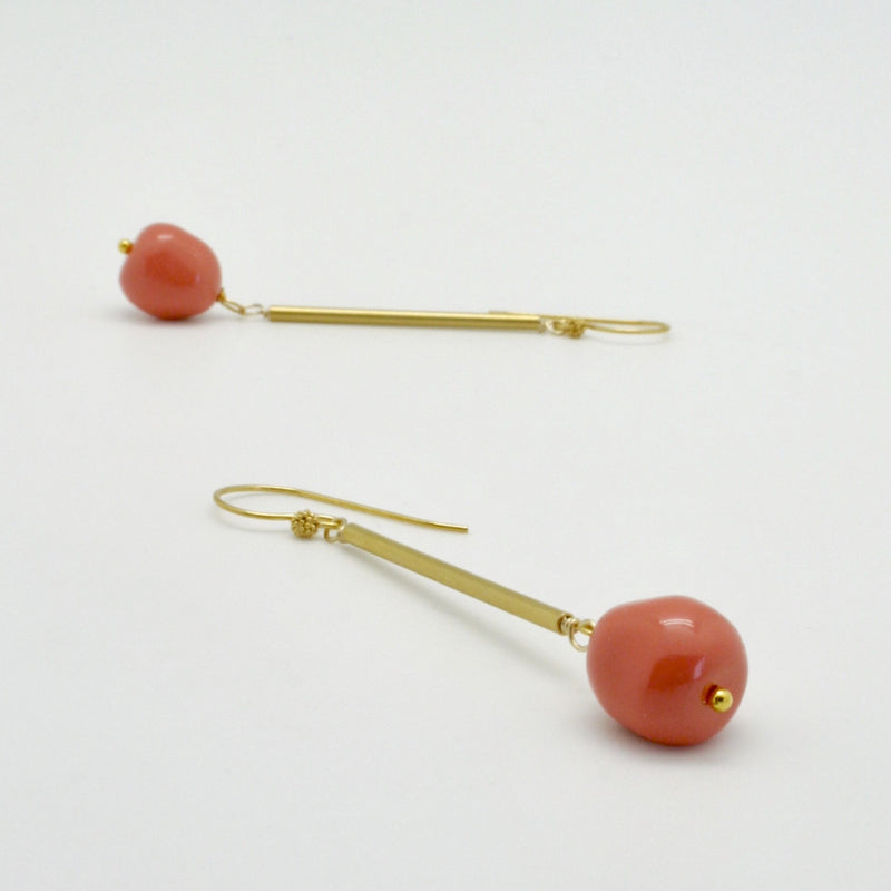 coral nugget earrings hanging from matte gold tubes