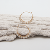 beaded ivory mini hoop earrings sitting on decorative plasterwork bark