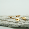 gold freeform disc chain earrings lying on decorative plasterwork bark by vivien walsh