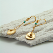disc chain earrings with jade bead lying on decorative plasterwork bark by vivien walsh