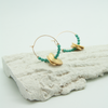 jade beaded midi hoop earrings sitting on plaster bark