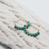 jade beaded mini hoop earrings lying on decorative plasterwork bark