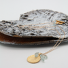 aquamarine dot disc necklace lying on decorative bark by vivien walsh