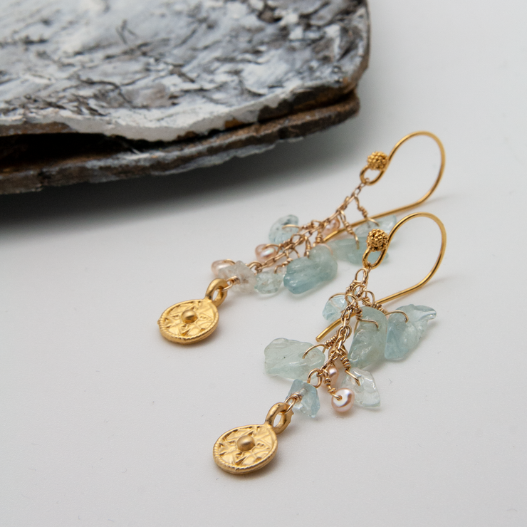 aquamarine waterfall earrings with freshwater pearls and gold coin charm lying flat