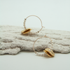 ivory beaded disc midi hoop earrings lying on decorative plasterwork bark