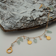 Aquamarine and gold coin charm bracelet lying over bark