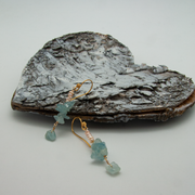 aqua vertical earrings with freshwater pearls lying on a decorative wooden heart
