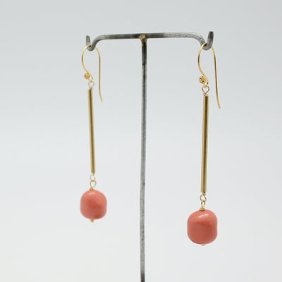 coral and gold tube earrings on stand