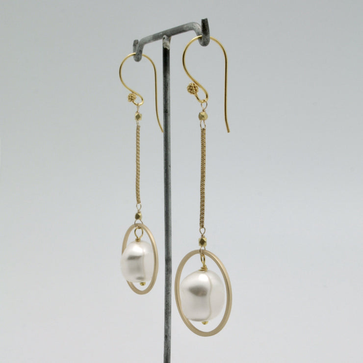 long matte gold chain earrings with white nugget pearls suspended within gold open circles
