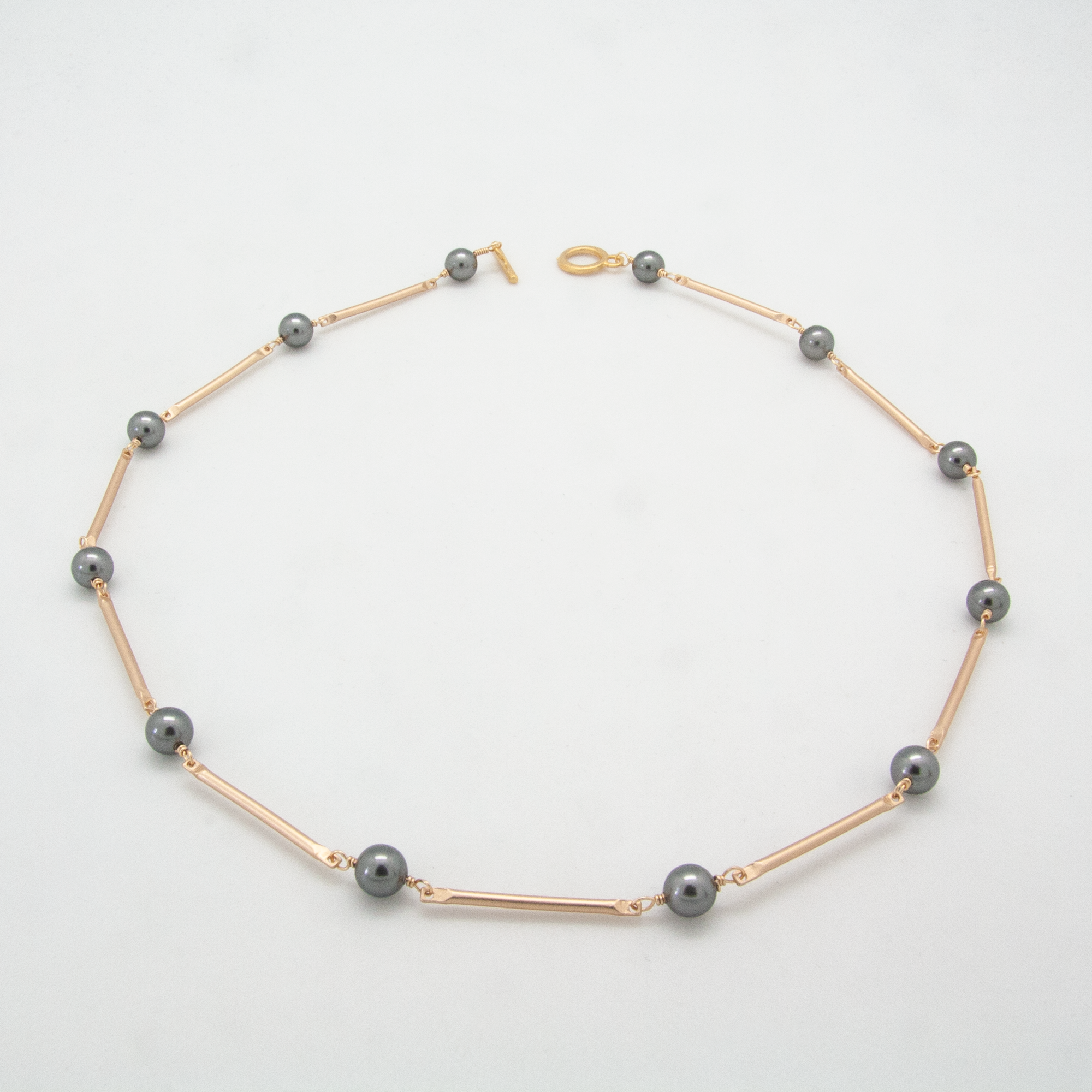 Matte gold bar necklace with Swarovski crystal dark grey pearls by vivien walsh