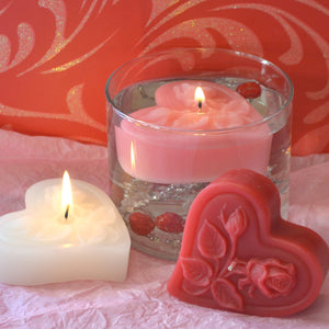 three floating heart candles with roses on top in pink, white and red floating in a clear glass cylinder for valentines day centerpieces