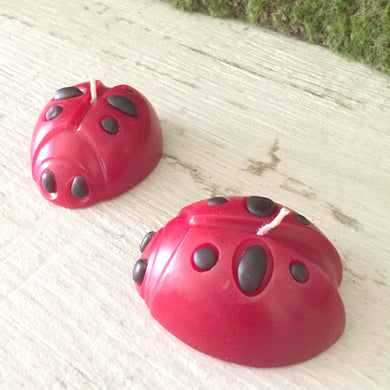 two red and black lady bug shaped candles